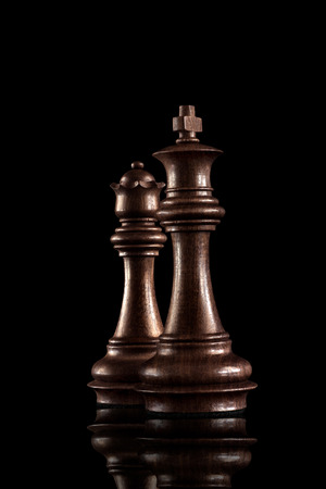 黒の木製王と女王は、暗い背景に一緒に立っている最も強力な人物のチェス ゲームのコンセプト。 写真素材