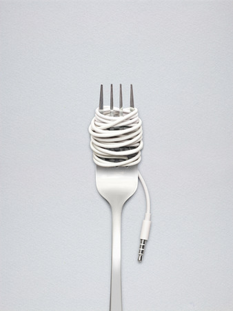 plug in: A shining fork with noodle made of cable with music jack plug in metal background.