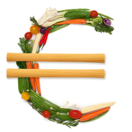 The euro money sign made of fresh healthy raw vegetables with two piles of noodles in the middle.