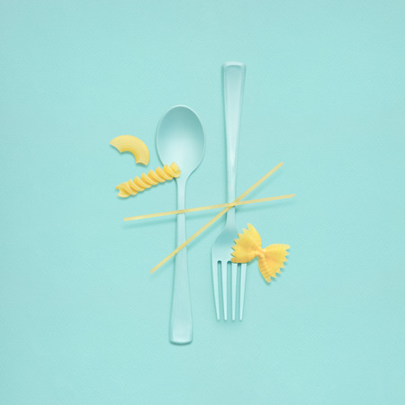 serving utensil: Creative still life of fork and spoon at a lunchtime with raw pasta served.