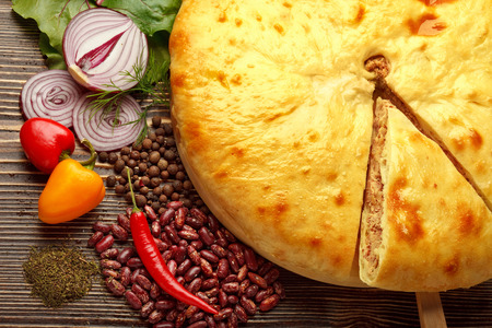 A colorful photo of traditional delicious beef osetinian pie. Kadurdjin meat pie and vegetables on wood.
