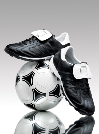 reflective: A pair of cool football boots standing on a ball on a reflective surface.