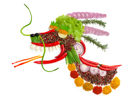 A food concept of a dragon made of spices isolated on white.