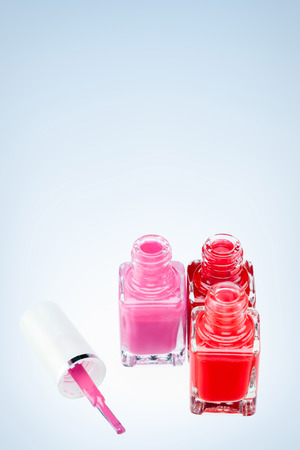 Three open nail polish bottles of different colors on a white surface with one pink brush.
