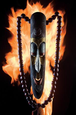 Un gros plan d'un ancien masque en bois avec des perles contre les flammes du feu. Banque d'images - 77060995
