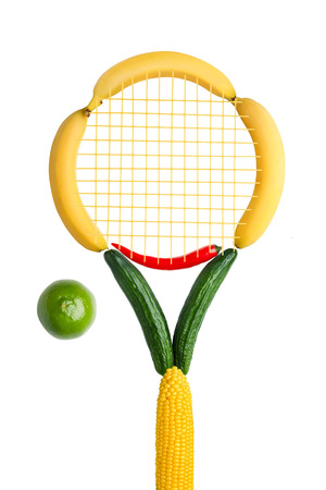 red chilly: A tennis racket made of fruits, vegetables and noodle net with a lime as a ball on white background.