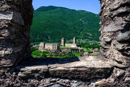 Castlegrande framed by ruined stone of Montebello Castle, Three Castles of Bellinzona, Ticino, Switzerland. Stock Photo