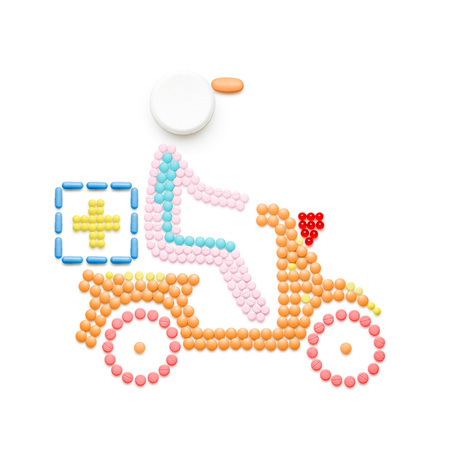 help: Creative medicine and healthcare concept made of pills, drugs motorbike delivery, isolated on white.