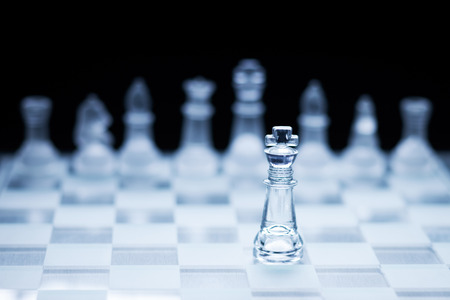 Photo of chess king standing in front of the other colour set in bright background.