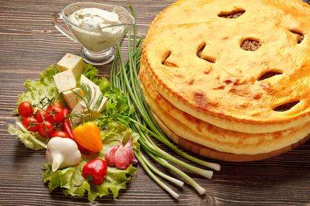 A colorful photo of traditional delicious beef osetinian pie. Heap of traditional Ossetian pies on wooden background.