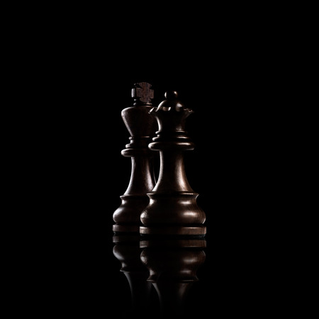 Chess game concept of black wooden king and queen, the most powerful figures standing together against dark background.
