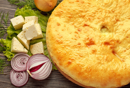 A colorful photo of traditional delicious beef osetinian pie. Kadyndzdzhin onion and cheese pie on wooden surface.