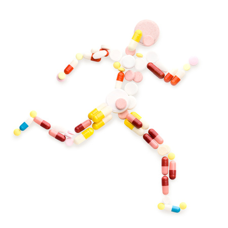 Doping drugs and pills in the shape of an athletic runner on track.