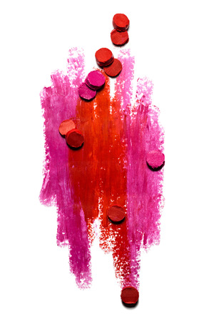 Creative photo of an abstract red and pink strokes with slices of lipstick isolated on white.