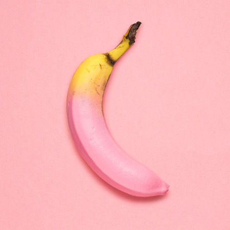 Creative photo of a painted banana on pink background.