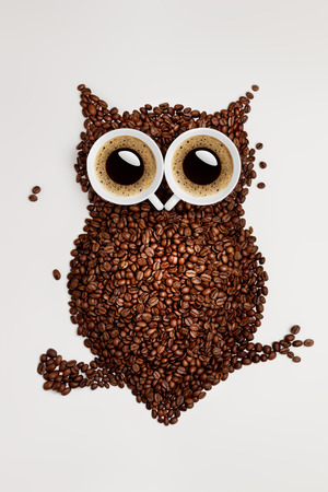 A funny owl made of roasted coffee beans and two cups.