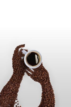 Creatieve koffieboonkunst; menselijke handen gemaakt van gebrande koffiebonen, met een kopje koffie op een grijze achtergrond.