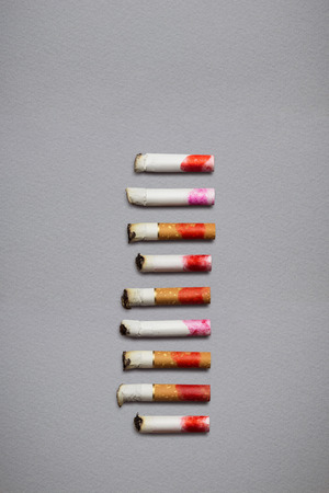 Creative still life of different cigarette stubs with lipstick on grey background.