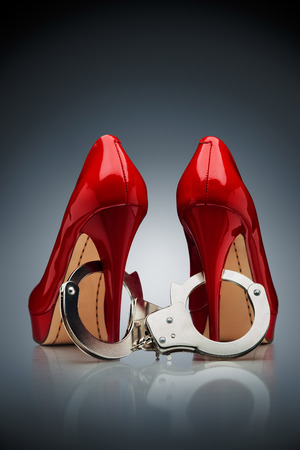 A beautiful abstraction, consist of two red heels cuffed with handcuffs in white to silver gradient background.