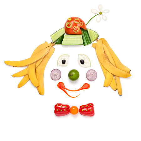 A creative food concept demonstrating a portrait of smiling clown made of vegetables and fruits in a menu for children. Imagens
