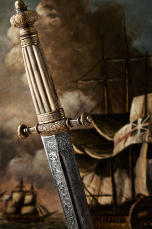 medieval blacksmith: A close-up of an ancient carved sword against painted background. A closeup view of the handle and the blade design of a Slavic dagger from 19th century. Stock Photo