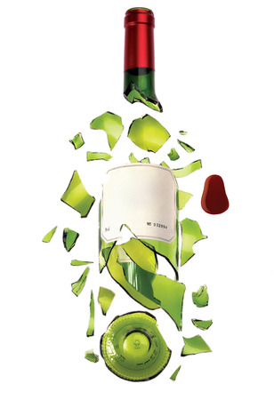 A bottle of wine made of green transparent glass with label and red top broken into pieces.