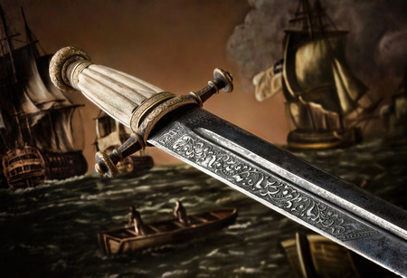 A close-up of an ancient carved sword against painted background. A closeup view of the handle and the blade design of a Slavic dagger from 19th century. Stok Fotoğraf