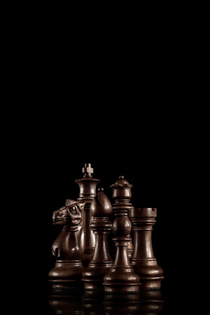 Strategy and leadership concept; black wooden chess figures standing together as a family ready for game against dark background.