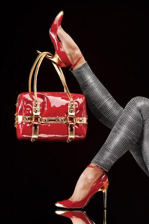 スタイリッシュな赤いバッグ シックなかかとの高い靴に掛かっています。