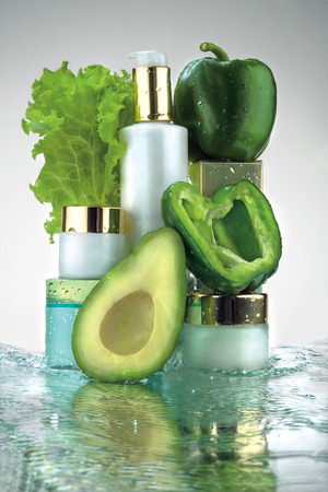 renew.: A close-up of different jars of cosmetics and green vegetables in water splash. Stock Photo