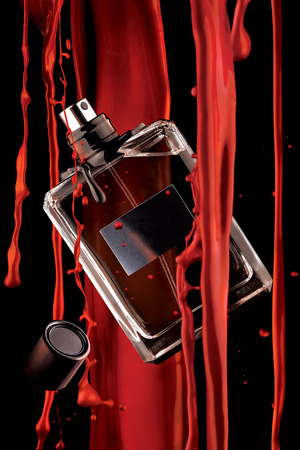 A stylish view of a bottle of male perfume and flowing red paint.