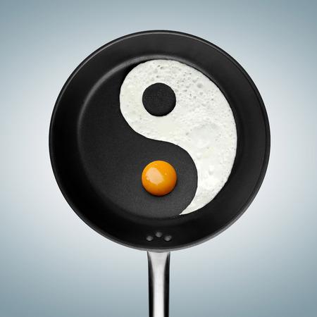 An yin-yan symbol made of fried egg in a pan. Banco de Imagens