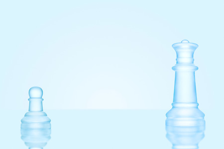 Leadership and bravery concept; an icy frosted single pawn staying against a queen on chessboard.