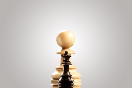 Leadership and bravery concept; huge white wooden pawn staying against a small black queen.