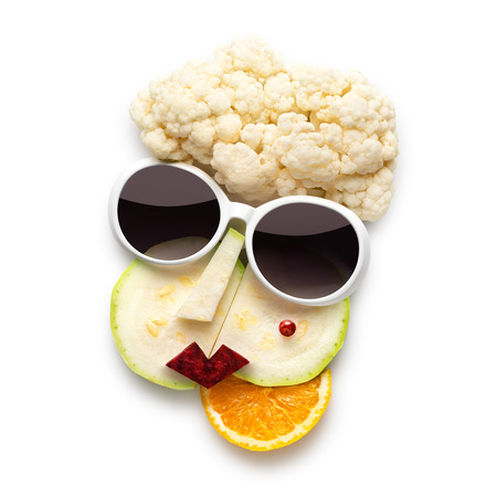 cubismo: Quirky food concept of cubist style female face in sunglasses made of fruits and vegetables, isolated on white.