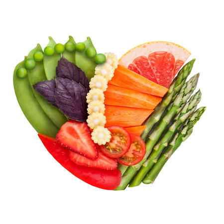 reduce risk: Healthy food concept of a human heart made of fresh vegetables and fruits that reduce death risk, isolated on white.