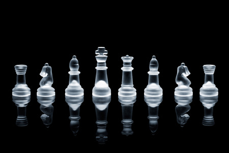 A set of semi transparent chess pieces on reflective surface.