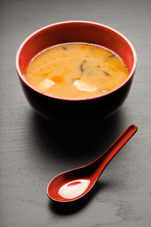 A close-up of a spoon and a soup plate with delicious miso soup.