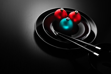 A black plate in a japanese sushi restaurant menu decorated with Christmas balls and chopsticks.