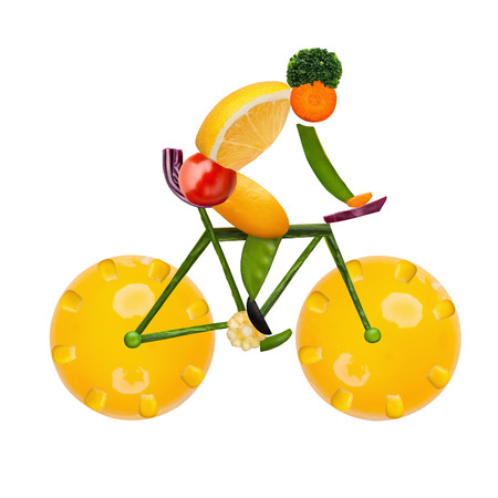 Healthy food concept of a male cyclist on a road bike made of fresh vegetables and fruits, isolated on white. Stock Photo