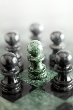 A composition made of pawn on the marble chess board.