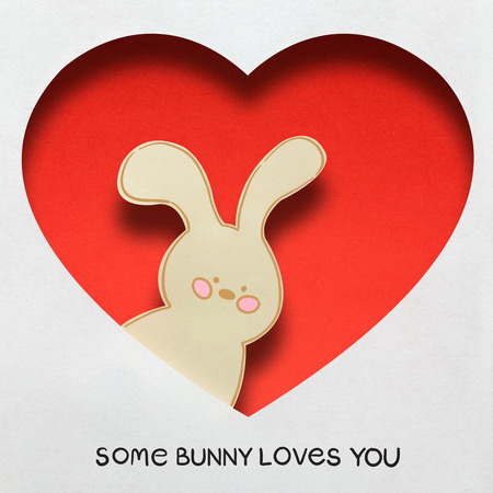 Creative concept photo of a bunny in a heart made of paper on white background.