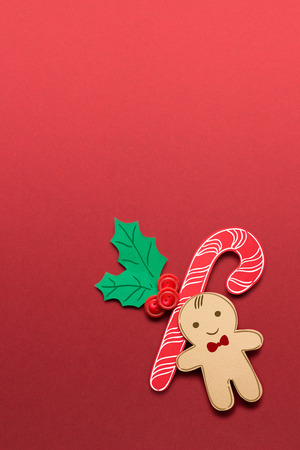 Creative concept photo of christmas candy and  gingerbread man on red background. Stock Photo