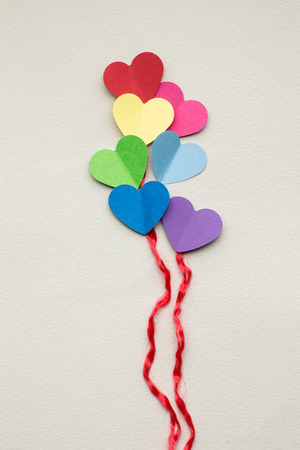 Creative valentines concept photo of hearts as balloons on grey background.