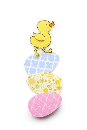Creative easter concept photo of a duck with eggs made of paper on white background.