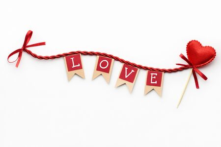 Creative valentines concept photo of flags with love sign and heart on the rope on white background.