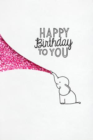 Creative birthday concept photo of illustrated elephant on white background.