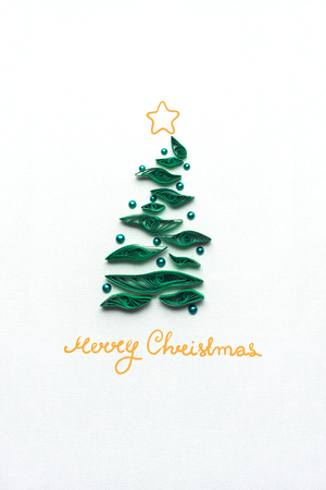 Creative concept photo of a christmas tree made of paper with beads on grey background. Stock Photo