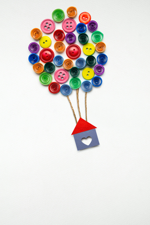 Creative concept photo of a house with air balloons made of paper on white background.