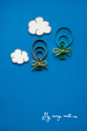 Creative concept photo of clouds and aerostats made of paper on blue background.
